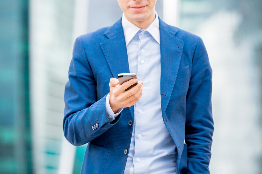 Handsome businessman in suit standing at the street with smart phone in hand and texting. Modern skyscrapers on the background.